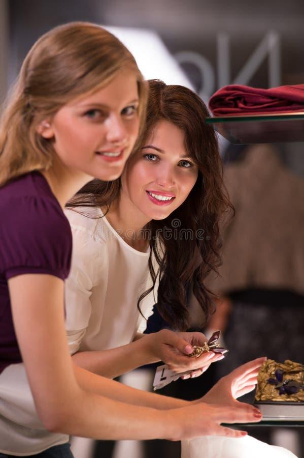 Två härliga unga flickor som väljer tillbehör på lagret royaltyfria foton
