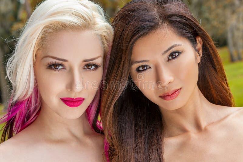 Två härliga unga kvinnor eller flickor en blondin och en kinesisk asiat royaltyfria bilder