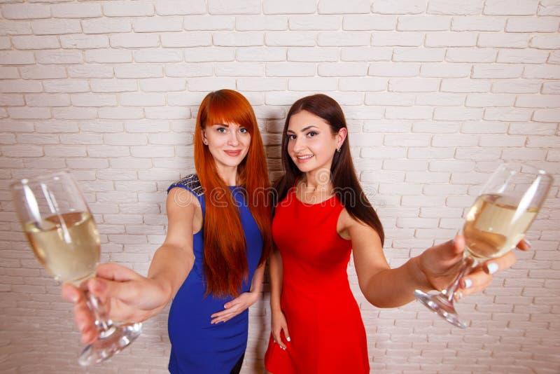 Två härliga unga kvinnor i afton bär att festa med champagn fotografering för bildbyråer