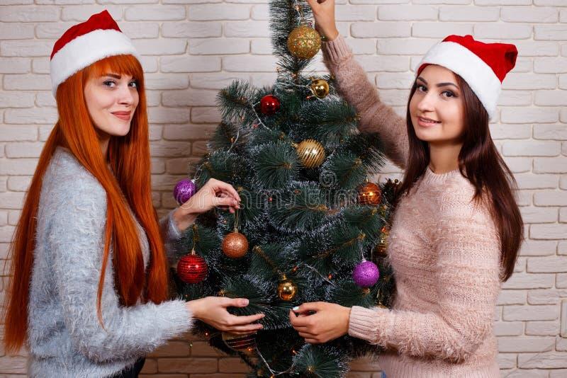 Två härliga unga kvinnor i julhattar som dekorerar jul arkivbild