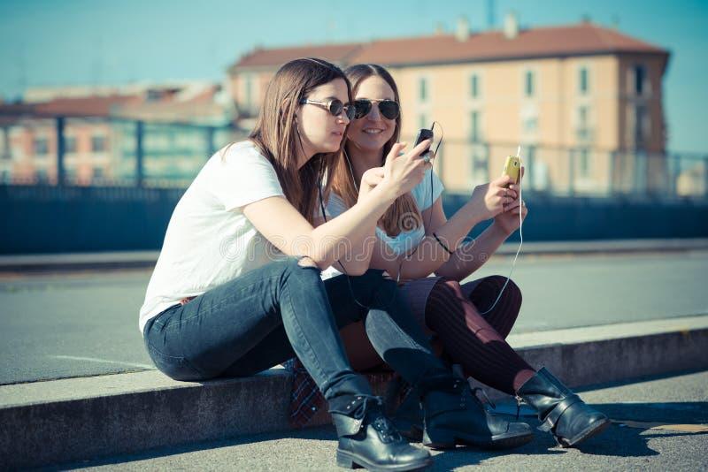 Två härliga unga kvinnor som använder den smarta telefonen fotografering för bildbyråer