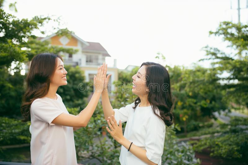 Två härliga unga kvinnor som ger höjdpunkt fem - nätta flickor som står på det fria och har gyckel - bästa flickvänner som gör et fotografering för bildbyråer
