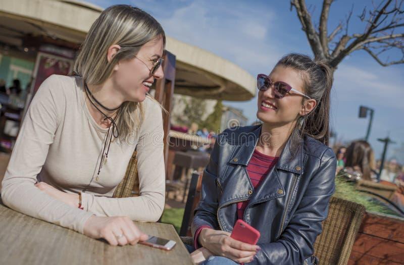 Två härliga unga kvinnor som har rolig det fria, medan genom att använda deras mobiltelefoner arkivbilder