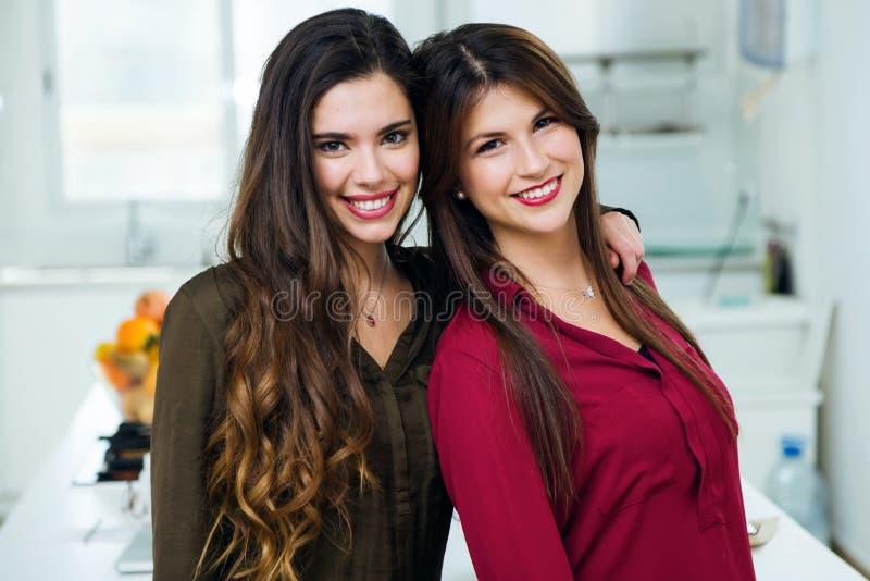 Två härliga unga kvinnor som ser kameran i köket arkivfoton