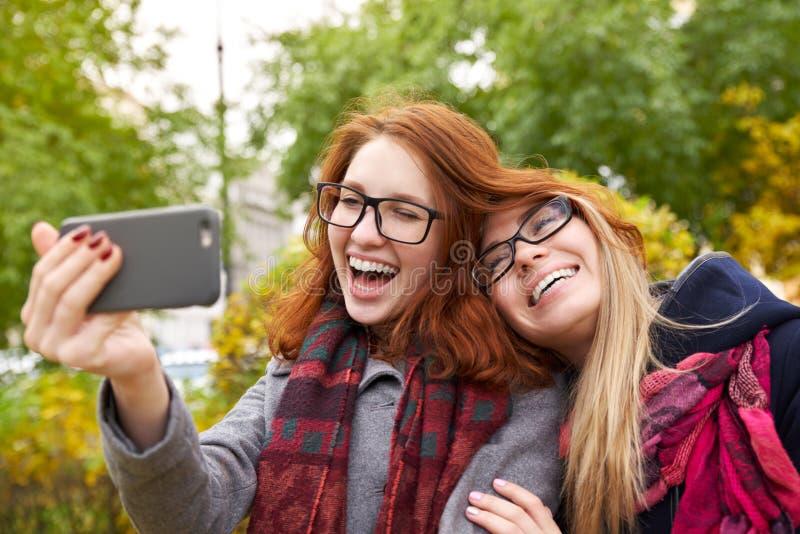 Två härliga unga kvinnor som tar selfies, medan gå i auen royaltyfria foton