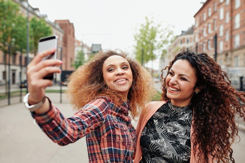 Två härliga unga kvinnor som tillsammans tar en bild arkivbild