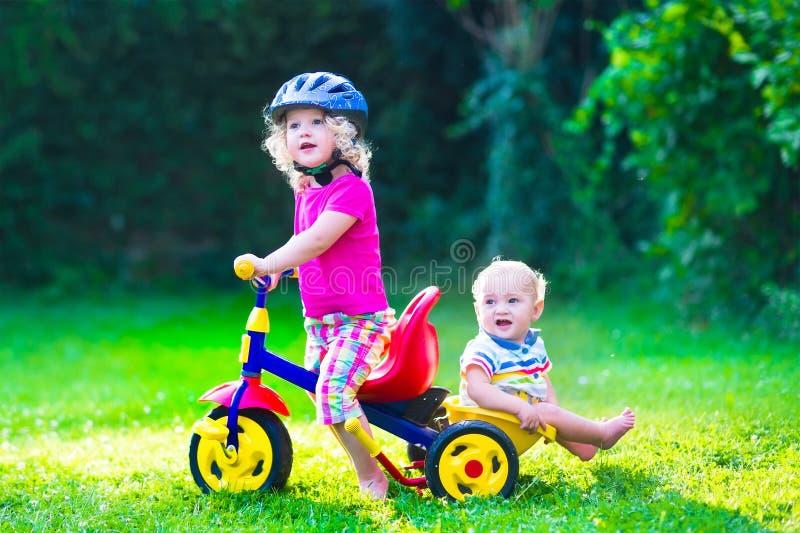 Två härliga ungar på en cykel royaltyfri bild