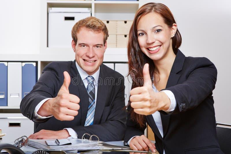 Två hållande tummar för affärsfolk arkivbild