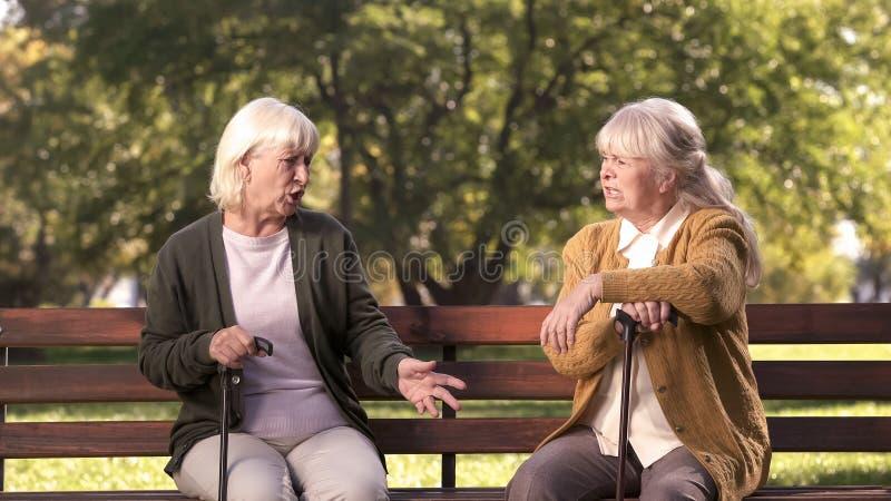 Två höga damer som argumenterar och sitter på bänk i, parkerar, vresiga fläder, tvist arkivbild