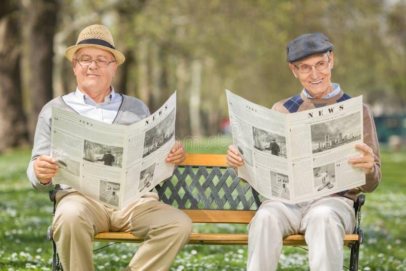 Två höga gentlemän som läser nyheterna arkivfoton