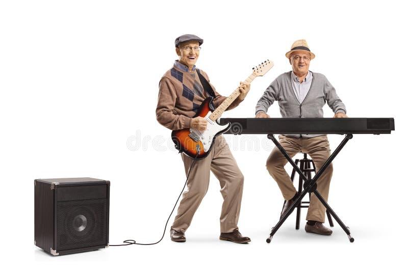 Två höga män som spelar tangentbordet och en elektrisk gitarr royaltyfri foto