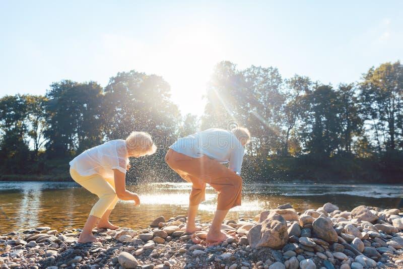 Två höga personer som tycker om avgång och enkelhet nära floden royaltyfri fotografi
