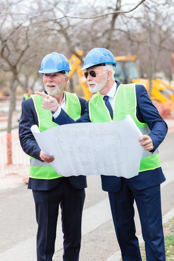 Två höga teknikerer eller affärsmän som besöker konstruktionsplatsen, ser ritningar och diskuterar arkivbild
