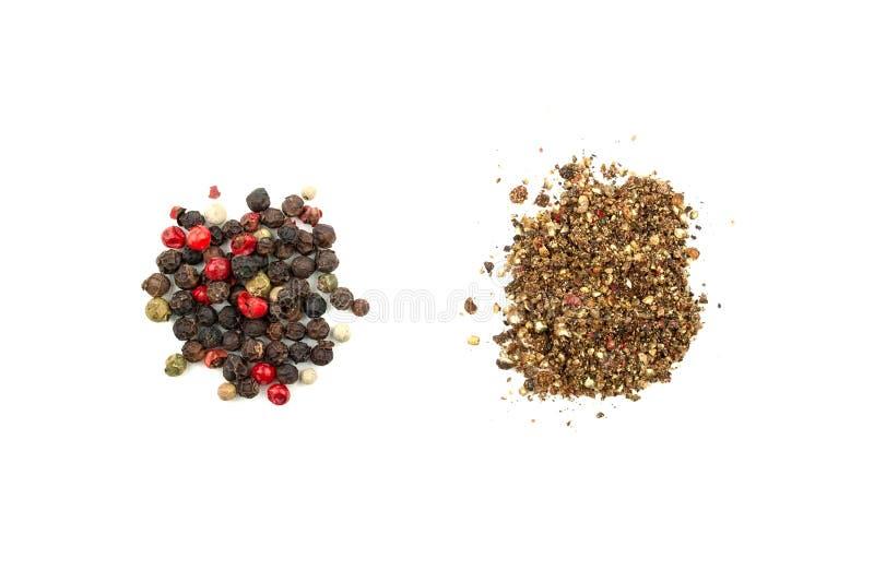 Två högar av pepparblandning: korn och jordning En blandning av fyra typer av pepparkorn: svart vitt, rosa, gr?nt B?sta sikt f?r  royaltyfri bild