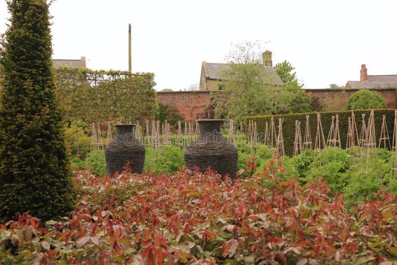 Två högg stenkrukor i walled trädgård royaltyfri foto