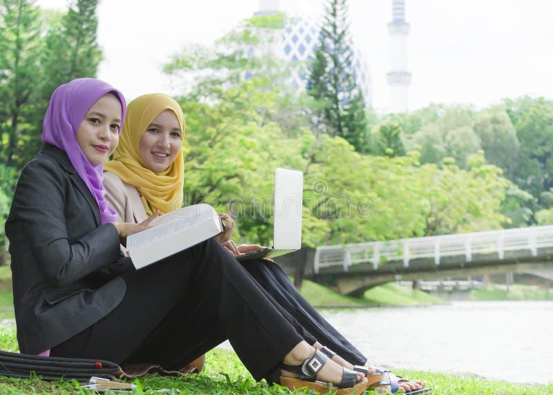 Två högskolestudenter som har diskussions- och ändraidéer, medan sitta i parkera arkivfoto