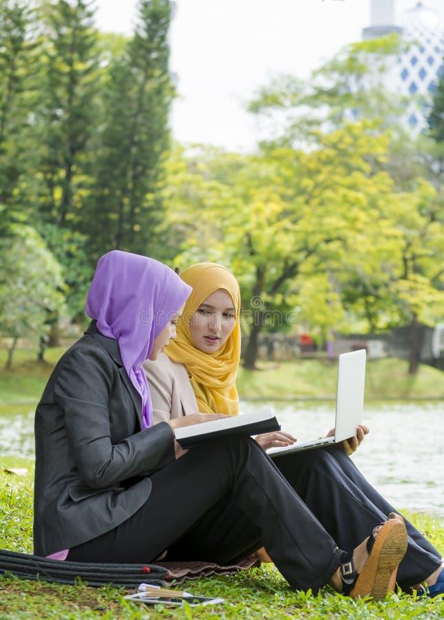 Två högskolestudenter som har diskussions- och ändraidéer, medan sitta i parkera royaltyfria bilder