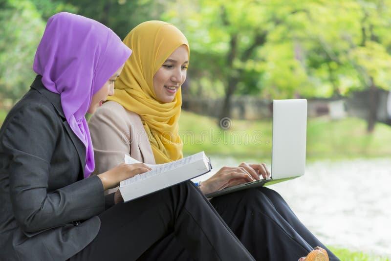 Två högskolestudenter som har diskussions- och ändraidéer, medan sitta i parkera fotografering för bildbyråer