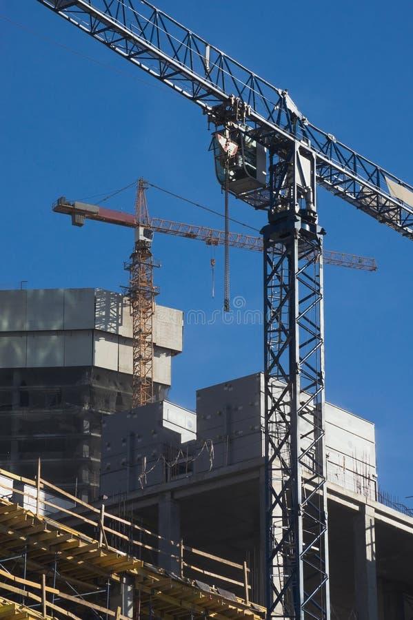Två höja kranar på konstruktionsplatsen arkivbild