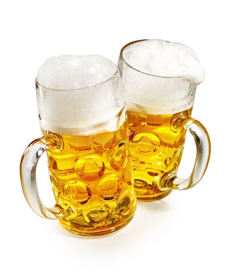 Två halv liter rånar av skummigt kallt öl royaltyfri foto