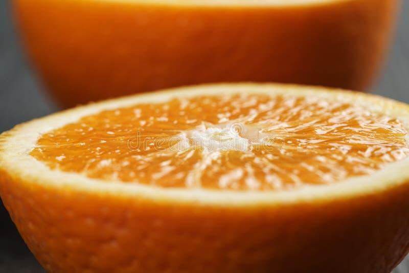 Två halvor av den mogna apelsinen på trätabellen arkivbild
