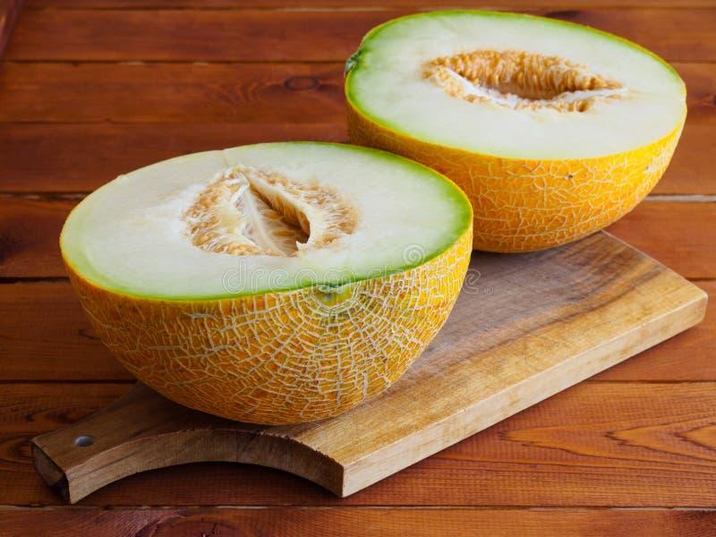 Två halvor av en melon på träbräde royaltyfria foton
