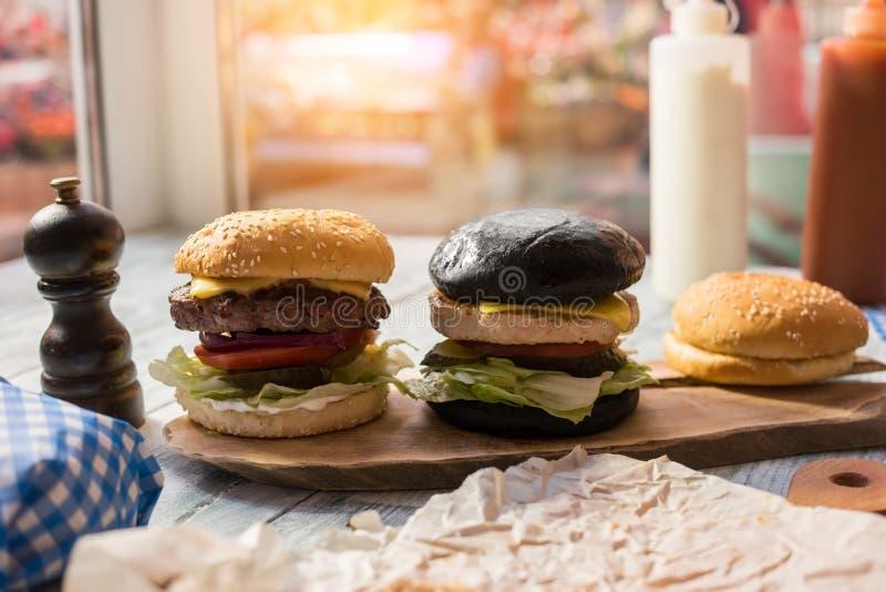 Två hamburgare på träbräde royaltyfria foton