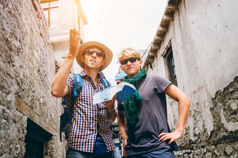 Två handelsresande som är borttappade i ändlös asiatisk gatalabyrint arkivfoto