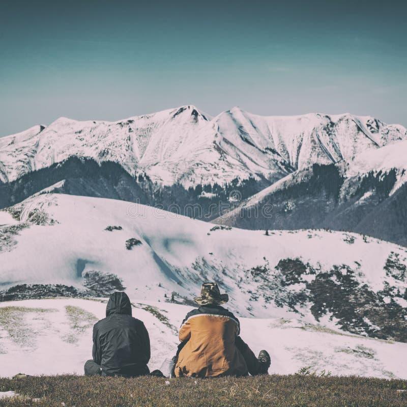 Två handelsresande som sitter på en kulle fotografering för bildbyråer