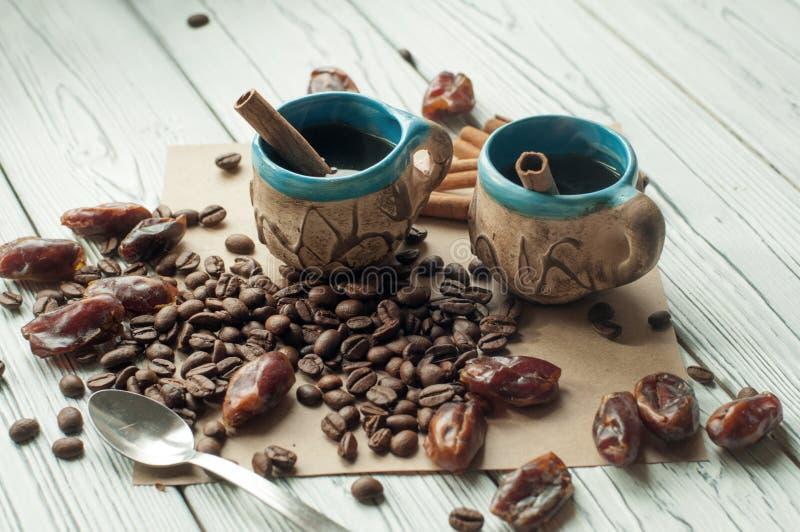 Två handgjorda koppar kaffe för liten gammal krukmakeri, kaffebönor, torkade data för sötsak och kanelbruna pinnar fotografering för bildbyråer