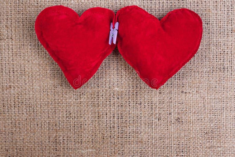 Två handgjorda röda tyghjärtor som fästas ihop med klädnypan på sackcl arkivfoton