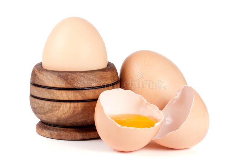 Två hela ägg och brutet ägg i en träbunke som isoleras på vit bakgrund royaltyfri bild