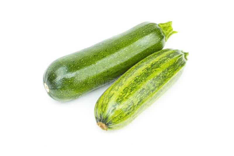 Två hela nya gröna mogna zucchini eller zucchinier, objekt som isoleras på vit bakgrund royaltyfri foto