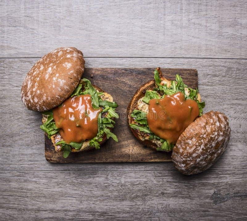 Två hem- hamburgare med höna i senapsgult sås, arugula, tomater på en skärbräda på trälantligt slut för bästa sikt för bakgrund u fotografering för bildbyråer