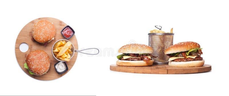 Två hemlagade hamburgare på träplattan som isoleras på svart bakgrund, två ostburgare på träplattan Frukost med hamburgare royaltyfri bild