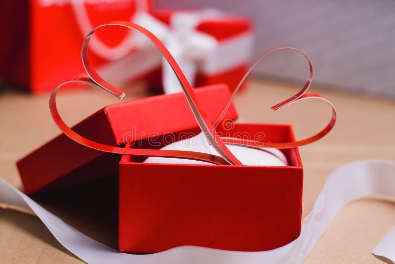 Två hemlagade pappers- röda hjärtor i en röd gåvaask, symbol av valentin dag royaltyfria foton