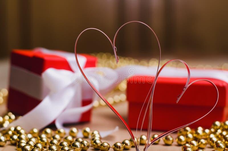 Två hemlagade pappers- röda hjärtor och röda gåvaaskar som binds med vita band arkivfoton