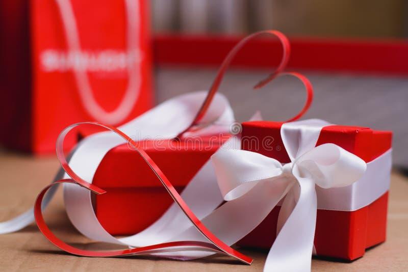 Två hemlagade pappers- röda hjärtor och röda gåvaaskar som binds med vita band, valentin dagsymbol arkivbilder