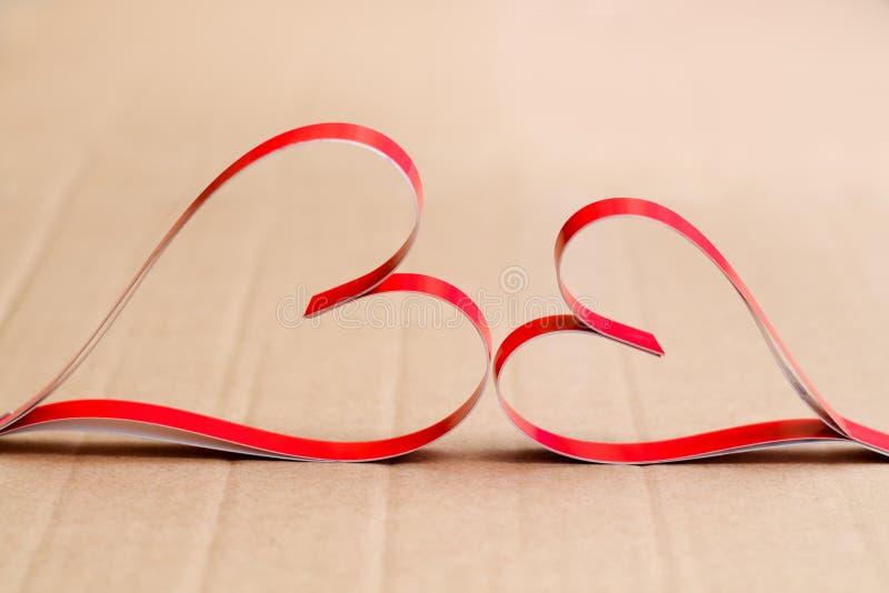 Två hemlagade pappers- röda hjärtor på en beige pappbakgrund, symbolet av valentin dag royaltyfria bilder