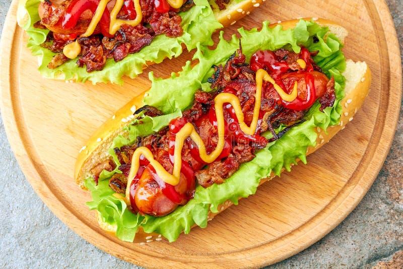 Två hemlagade varmkorvar med grönsallat-, bacon- och löktoppningar fotografering för bildbyråer