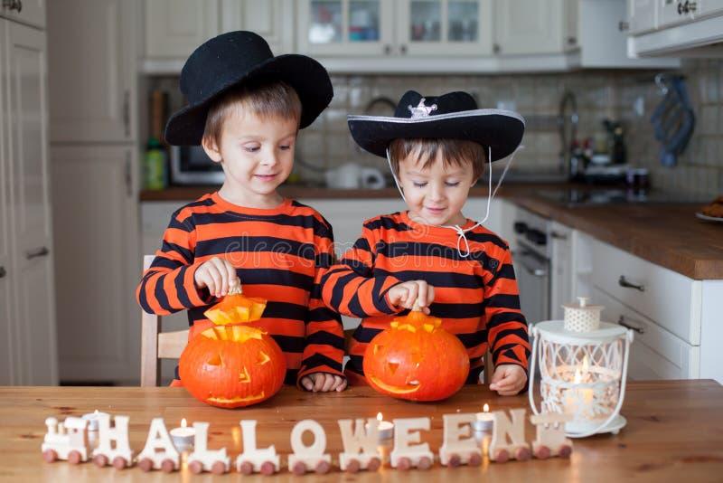 Två hemmastadda pojkar och att förbereda pumpor för halloween arkivbilder