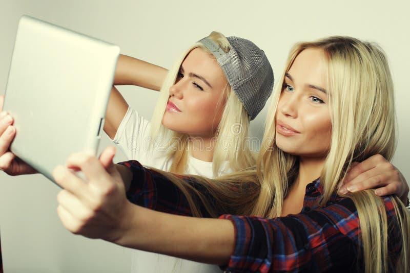 två hipsterflickavänner som tar selfie med den digitala minnestavlan, s royaltyfri fotografi