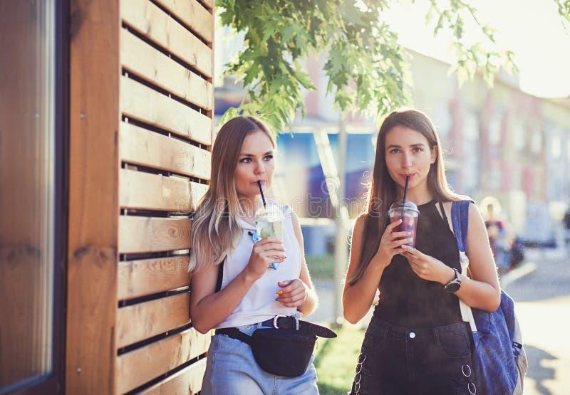 Två hipsterflickor med drinkar arkivbilder