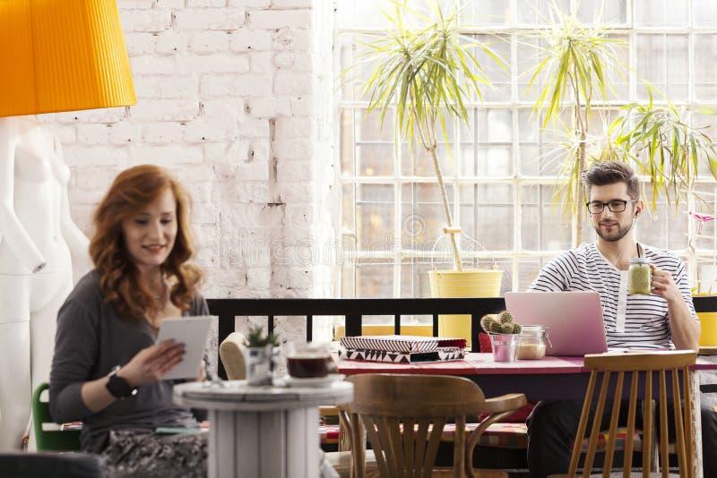 Två hipsters som arbetar i modernt kafé royaltyfria foton