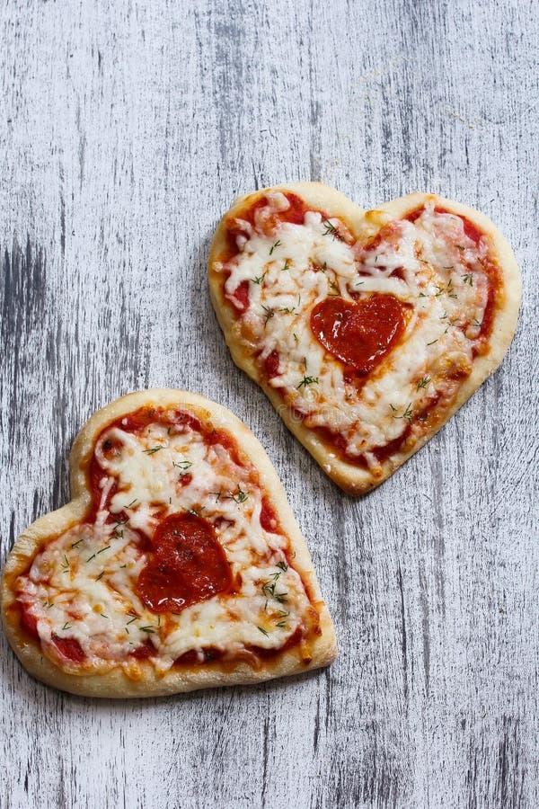 Två hjärta formad pizza för valentin dag arkivfoton