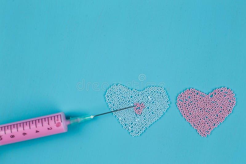 Två hjärtor av pärlor och den medicinska injektionssprutan, injektion som faller i l royaltyfria foton