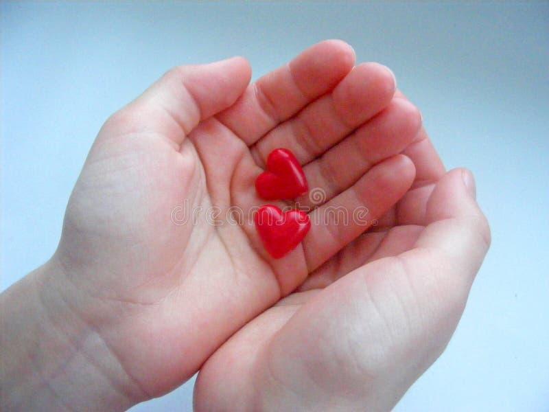 Två hjärtor i barnhänderna royaltyfria bilder