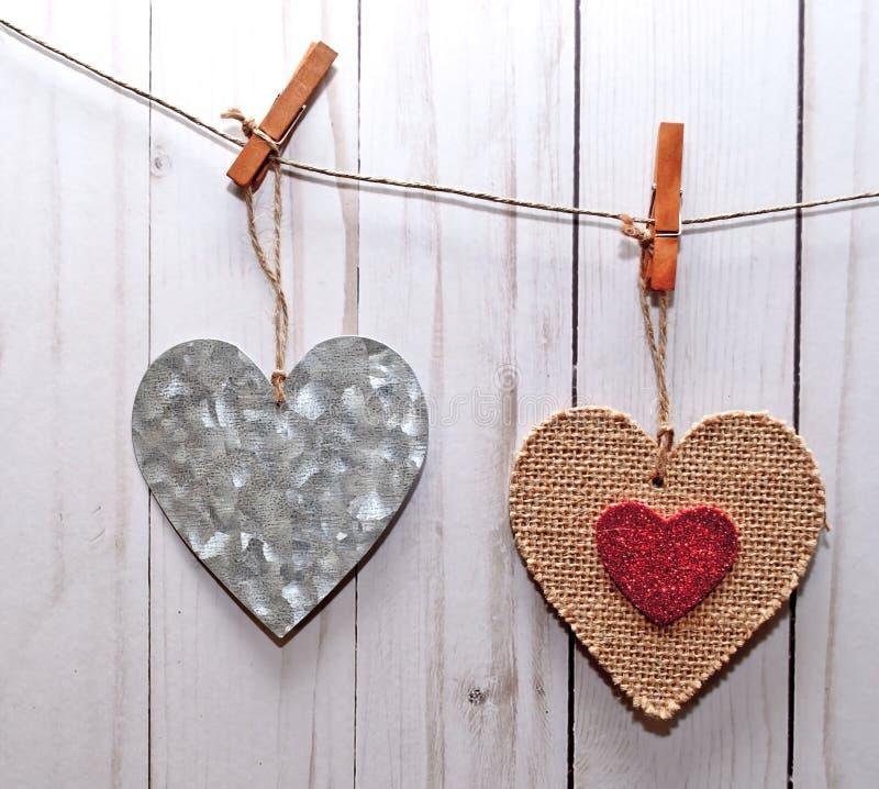 Två hjärtor på en linje framme av ett vit tvättat staket royaltyfri fotografi