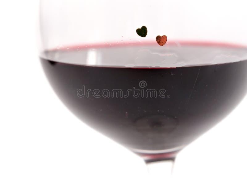 Två hjärtor på ett exponeringsglas med rött vin på vit bakgrund fotografering för bildbyråer