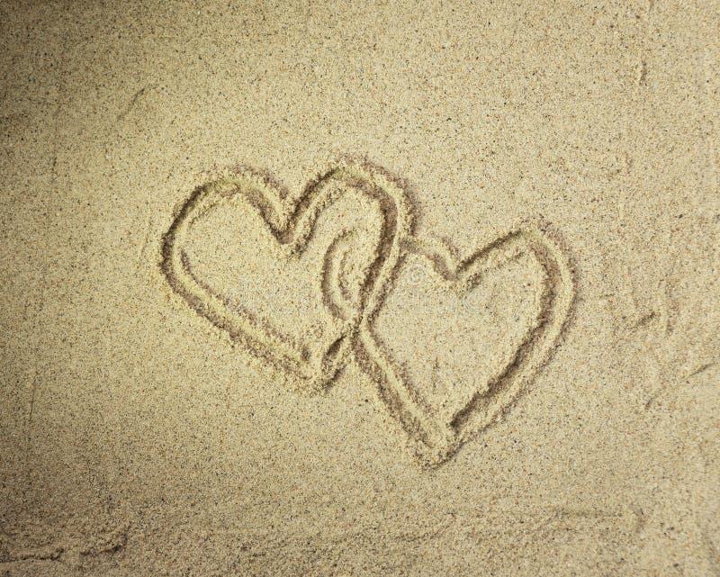 Två hjärtor som tecknas i strand 免版税库存图片